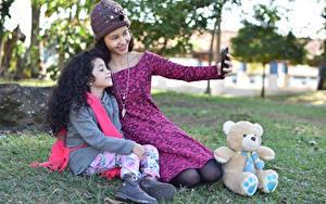 Фотографии Плюшевый мишка Мать Траве 2 Брюнетки Шапка Сидящие Селфи Улыбается Девочка ребёнок