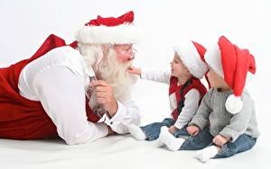 Обои Втроем Белый фон Сидящие Мальчики Свитера Дед Мороз Шапка Очках Борода Дети