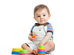 Фото Игрушки Белый фон Мальчишка Младенцы Смотрят Сидит Ребёнок