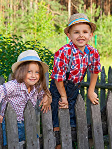 Фотографии Двое Мальчишки Девочка Забор Улыбается Шляпа Дети