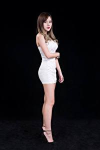 Фотографии Азиаты Шатенки Платье Белая Ноги Взгляд Черный фон Девушки