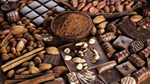 Фотография Сладости Шоколад Орехи Конфеты Корица Какао порошок Еда