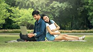 Фотография Мужчины Азиаты Студентки Ноутбуки Трава Сидящие 2 Девушки