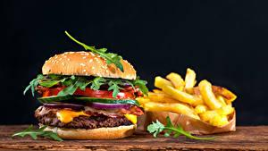Обои для рабочего стола Быстрое питание Гамбургер Булочки Картофель фри Овощи На черном фоне Еда