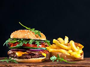 Картинка Быстрое питание Гамбургер Булочки Картофель фри Овощи На черном фоне