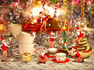 Картинка Рождество Свечи Огонь Праздники Дед Мороз Шапки Сидит Чашка