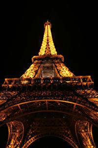 Обои для рабочего стола Франция Эйфелева башня Ночные Париже Вид снизу Черный фон Города