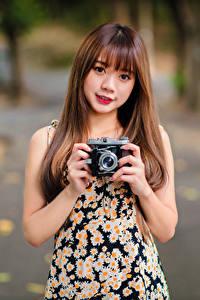 Фото Азиатки Шатенки Размытый фон Фотокамера Руки Взгляд Девушки