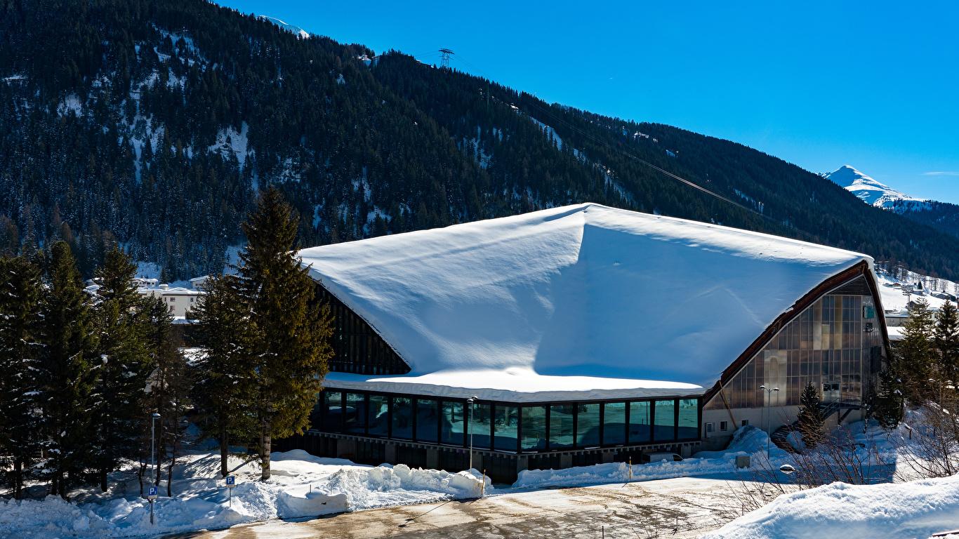 Картинка Швейцария Davos гора зимние снегу город Здания 1366x768 Горы Зима Снег снеге снега Дома Города