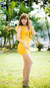 Обои для рабочего стола Азиаты Позирует Платья Желтый Ноги молодая женщина