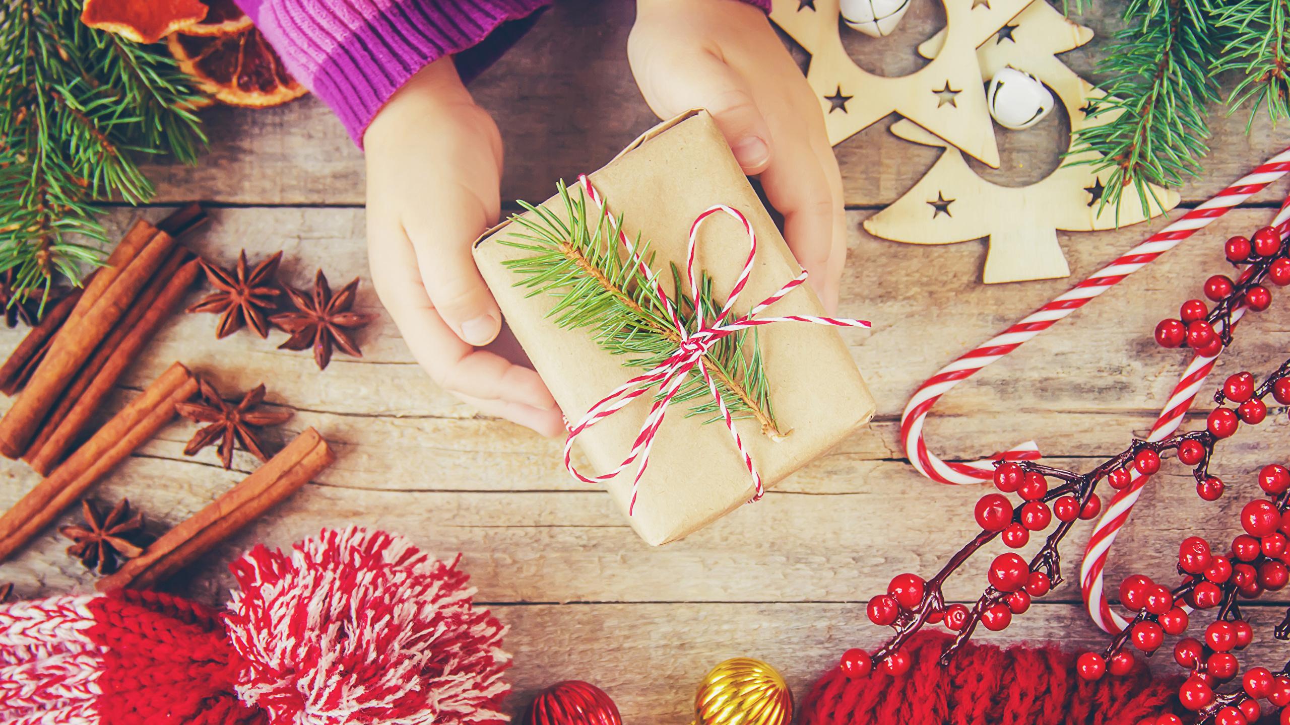 Фотографии Рождество Бадьян звезда аниса Корица Подарки Руки Ягоды сладкая еда Доски 2560x1440 Новый год подарок подарков рука Сладости