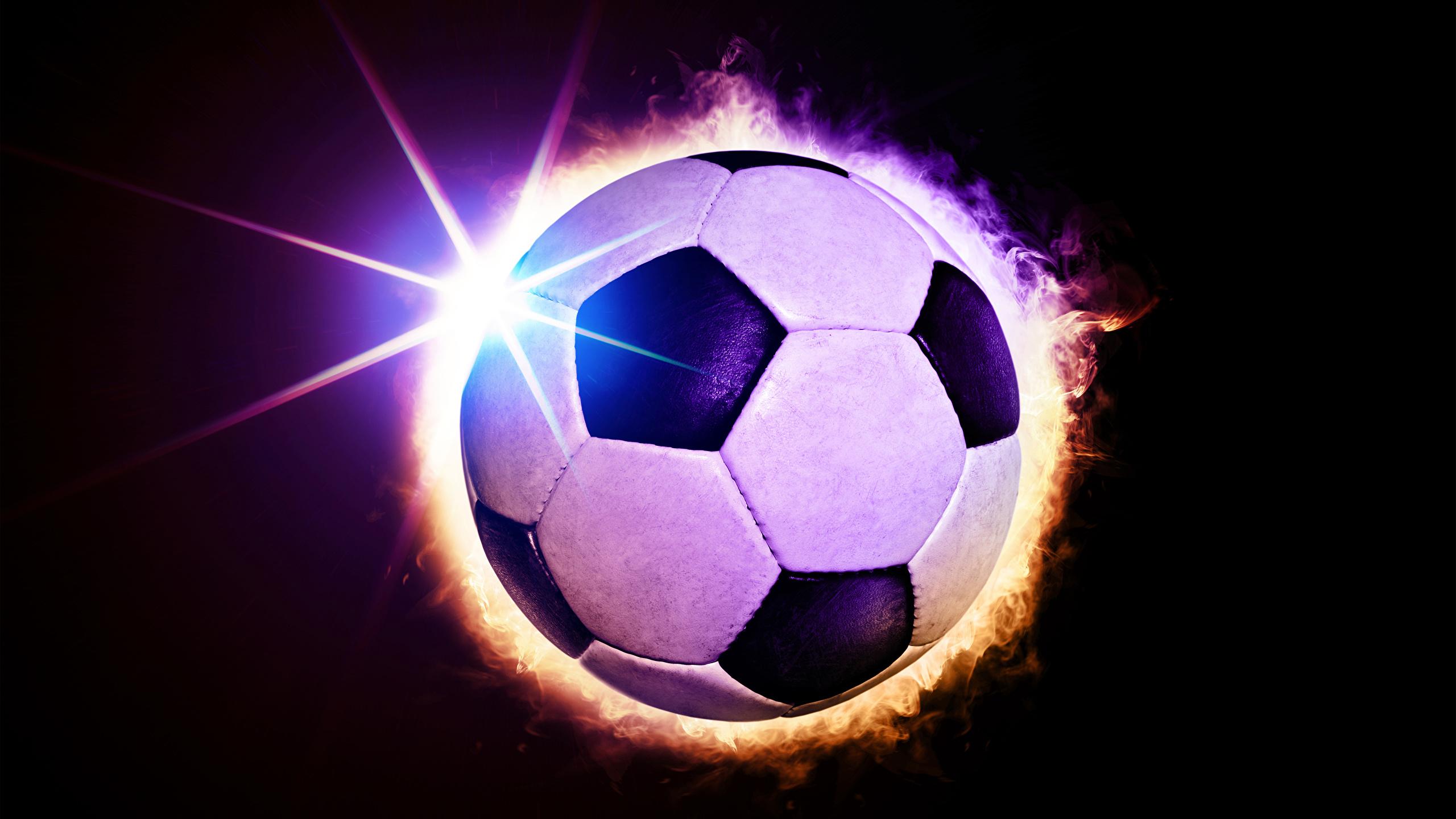 Фотографии Лучи света Футбол спортивный Мяч Черный фон 2560x1440 Спорт спортивная спортивные Мячик на черном фоне
