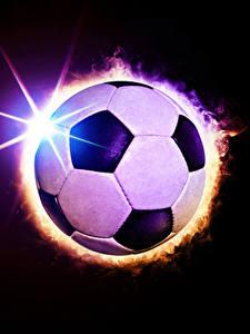 Фотографии Футбол Черный фон Мяч Лучи света Спорт