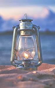 Фотографии Керосиновая лампа Крупным планом Огонь Размытый фон Песка