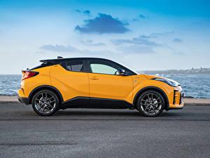 Картинки Тойота Кроссовер Желтая Металлик Сбоку Гибридный автомобиль C-HR Hybrid GR Sport, AU-spec, 2020 автомобиль