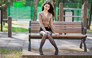 Картинки Азиаты Брюнеток Скамья Сидит Ноги Юбки Блузка Смотрят молодые женщины
