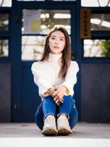 Фотографии Азиатки Сидя Джинсы Свитер Смотрят девушка