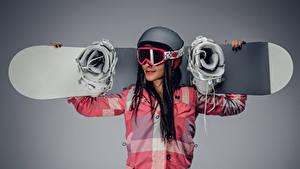 Картинка Сноуборд Сером фоне Шатенка Шлем Очков девушка Спорт