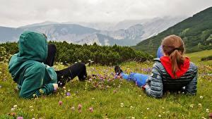 Картинки Горы Австрия Альпы Трава Двое Рыжая Отдых Куртка Капюшон