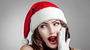 Фото Новый год Серый фон Шатенка Шапки Руки Взгляд Удивление Девушки