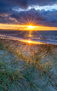 Обои Англия Пейзаж Рассветы и закаты Побережье Камень Облака Солнце Bournemouth Природа