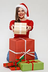 Картинка Рождество Серый фон Шатенка Улыбка Смотрит Шапки Подарки Девушки