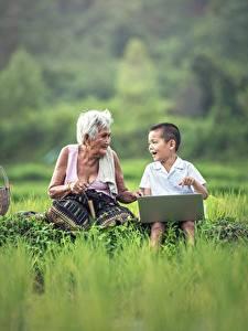 Фотографии Азиаты Трава Мальчики Ноутбуки Сидящие 2 Пожилая женщина Ребёнок
