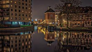Картинка Нидерланды Дома Реки Мосты Ночь Уличные фонари Groningen город