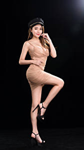 Картинки Азиатка Черный фон Поза Платье Ног Шатенки Взгляд Фотомодель