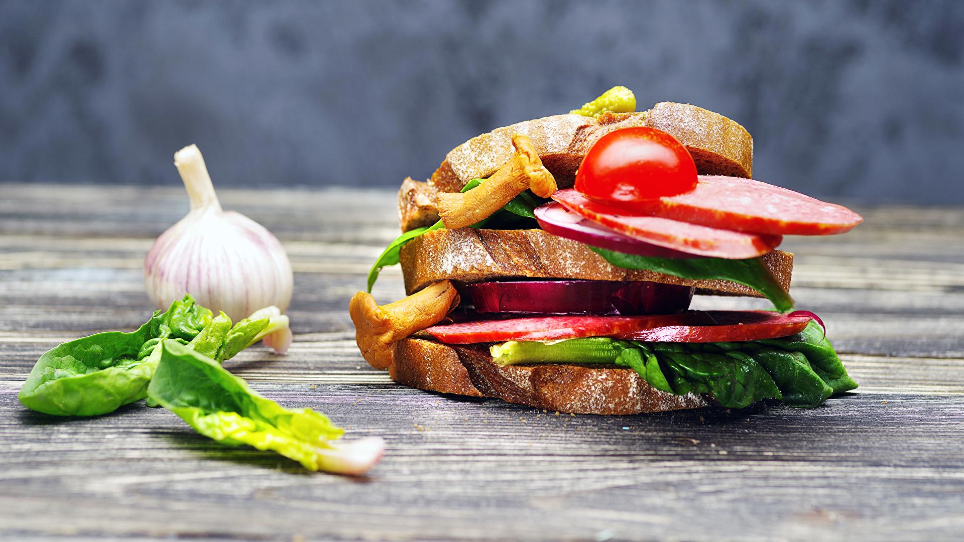 Картинки Колбаса Сэндвич Хлеб Чеснок Пища Овощи 1920x1080 Еда Продукты питания