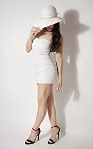 Фотографии Сером фоне Фотомодель Позирует Шляпы Платья Ног Туфель девушка