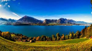 Картинка Швейцария Пейзаж Горы Озеро Побережье Осень Здания Луга Lake Thun Природа
