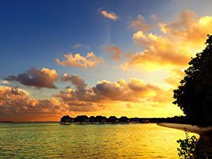 Фотографии Тропики Мальдивы Рассветы и закаты Море Небо Бунгало Облака Природа