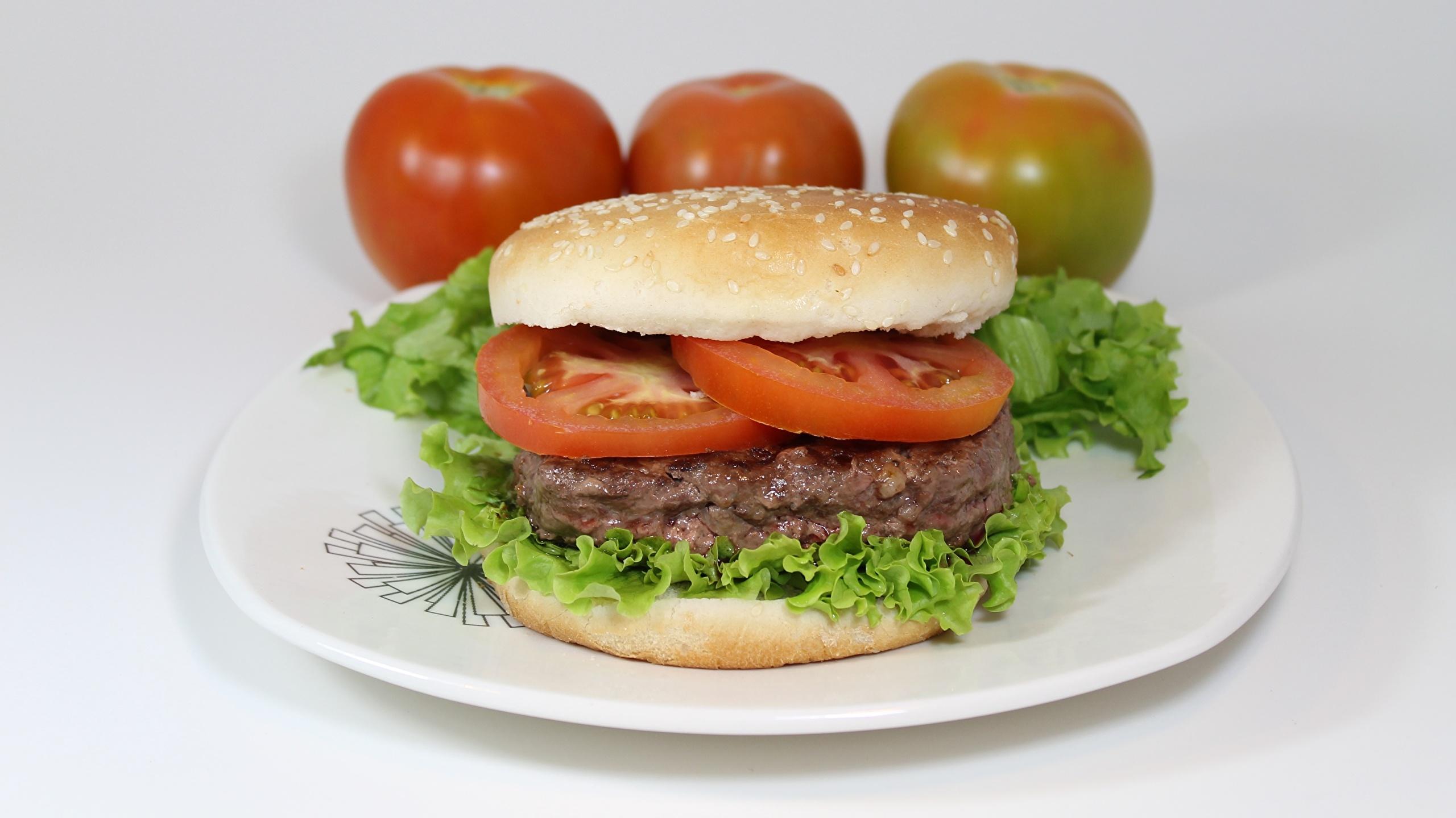 Фото Помидоры Гамбургер Еда Тарелка Нарезанные продукты Мясные продукты 2560x1440 Томаты Пища нарезка тарелке Продукты питания