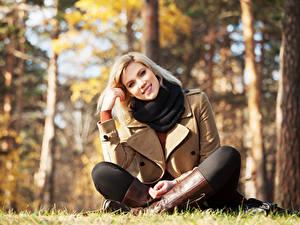 Фото Осень Блондинок Размытый фон Улыбается Сидящие Смотрит Сапог Позирует молодая женщина