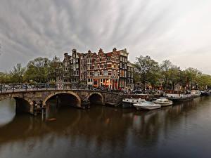 Фото Нидерланды Амстердам Здания Мосты Пирсы Вечер Корабли Речные суда Водный канал Города