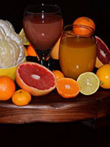 Фотография Цитрусовые Апельсин Лимоны Сок Мандарины Грейпфрут Черный фон Стакан