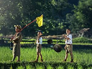 Фотографии Азиаты Мальчики Шляпа Шорты Трава Втроем Ребёнок