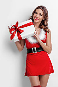 Фотографии Новый год Белый фон Шатенка Улыбка Платье Подарки Девушки