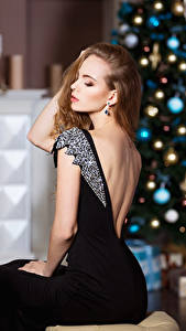 Фотографии Рождество Шатенка Елка Платье Сидя молодые женщины