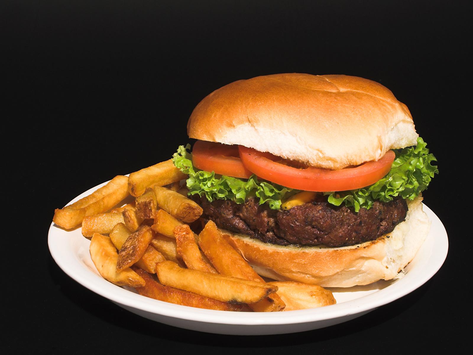 Картинки Гамбургер Картофель фри Фастфуд Булочки Еда тарелке на черном фоне 1600x1200 Быстрое питание Пища Тарелка Продукты питания Черный фон