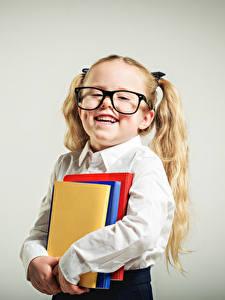 Фотографии Школа Серый фон Девочки Книга Очки Улыбка Ребёнок