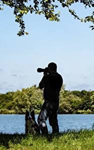 Фотографии Озеро Собаки Мужчины Трава Фотограф Природа
