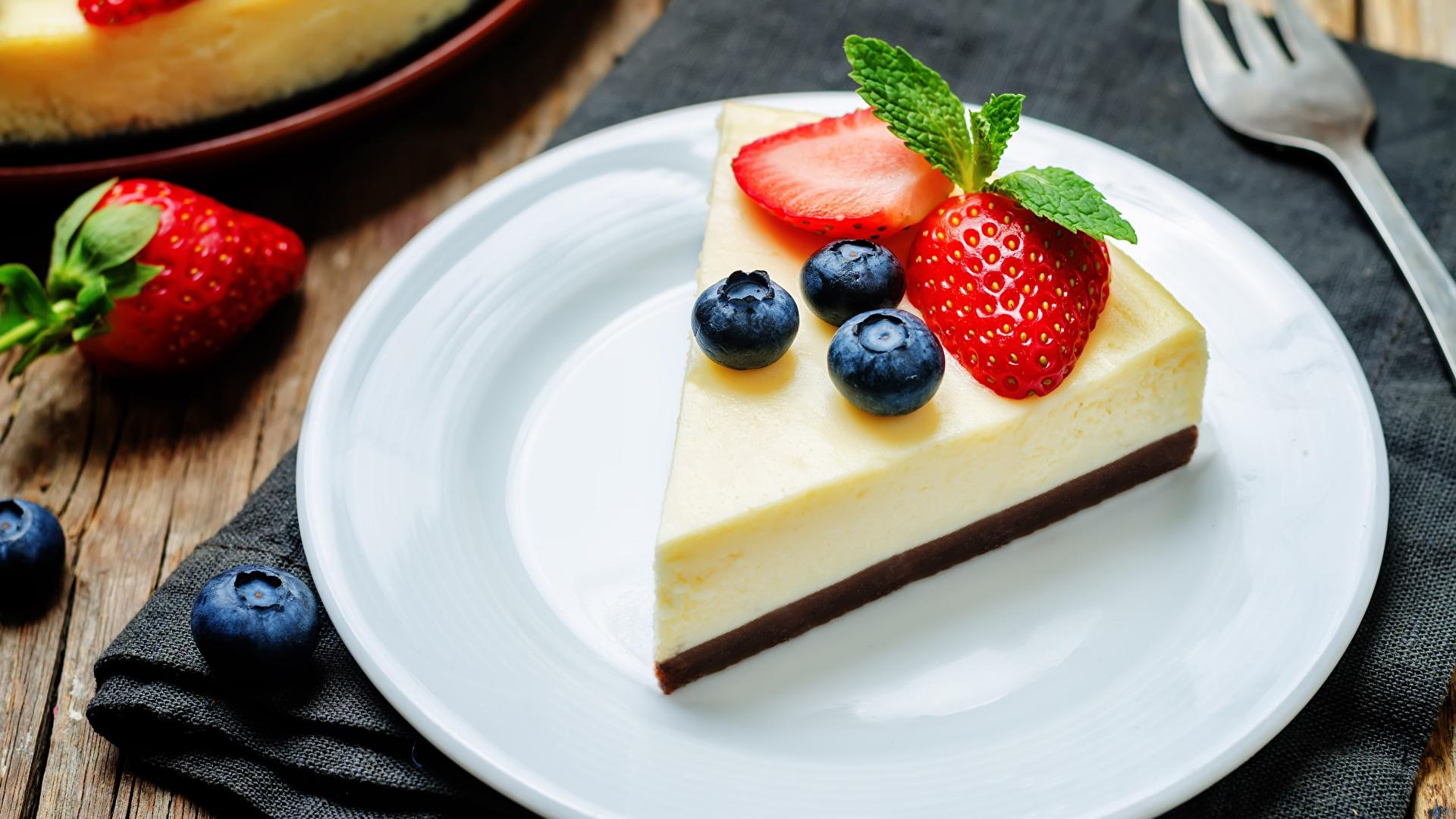 Фотография Cheesecake Десерт Черника кусочек Клубника Еда Тарелка 1920x1080 часть Кусок кусочки Пища тарелке Продукты питания