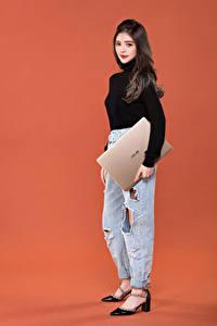 Картинка Цветной фон Туфель Джинсов Ноутбук Шатенки Смотрит кофточка девушка Компьютеры