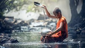 Фотографии Камни Азиатка Ручей Лысый Мальчики Сидя Брызги ребёнок