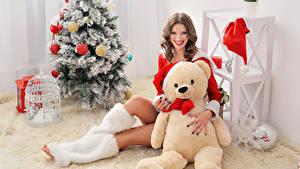 Фотографии Рождество Плюшевый мишка Шатенка Елка Улыбка Смотрит Сидящие