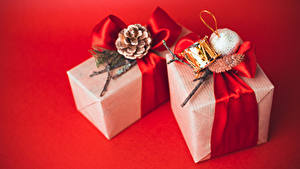 Фотографии Новый год Подарки Шарики Шишки Красный фон