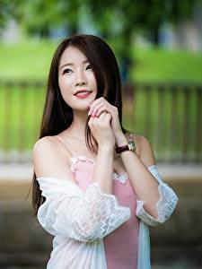 Фото Азиатка Размытый фон Шатенка Рука Смотрит Улыбка молодая женщина