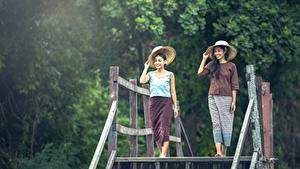 Картинка Азиаты Двое Брюнетка Шляпа Улыбка Девушки